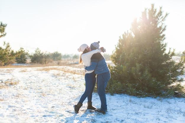 Liebespaar schneebälle spielen im winter im wald. Premium Fotos