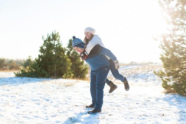 Liebespaar spielen im winter im wald. Premium Fotos