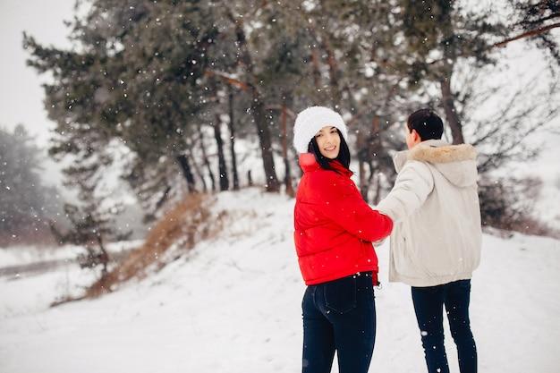 Liebespaar zu fuß in einem winterpark Kostenlose Fotos