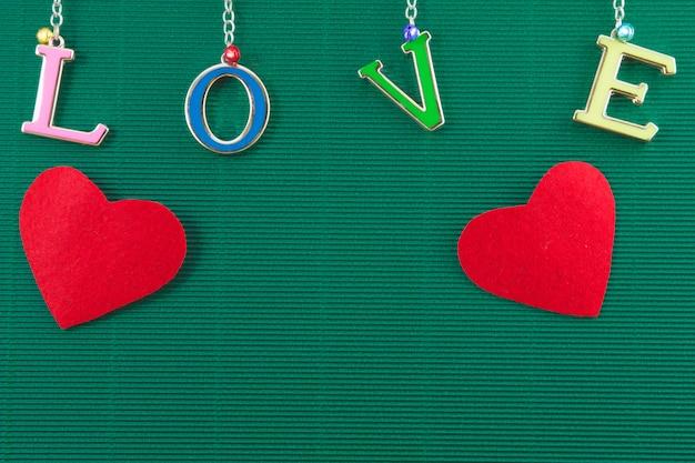 Liebestextnachricht mit 2 herzen hängen am grünen hintergrund, valentinsgrußkonzept Premium Fotos
