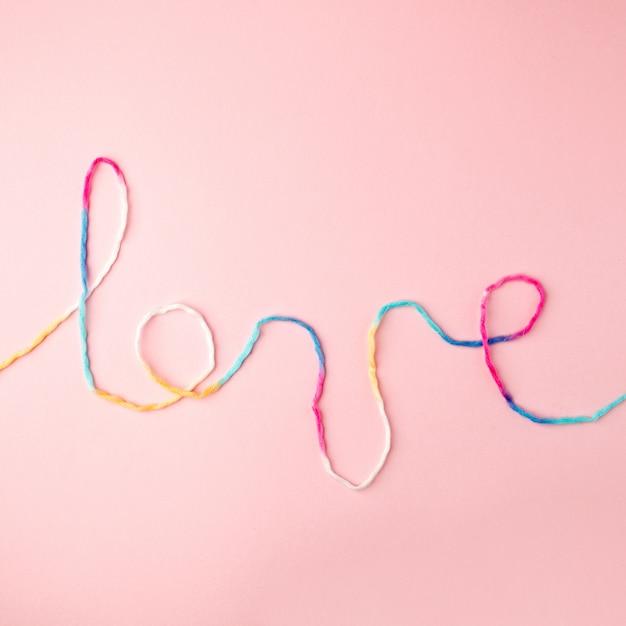 Liebeswort geschrieben mit garnbeschriftung, -konzept und -hintergrund für valentinstag Premium Fotos
