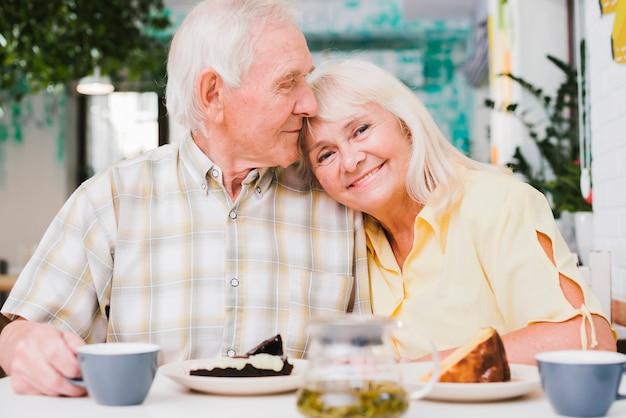 Liebevolle ältere paare, die tee mit kuchen trinken Kostenlose Fotos