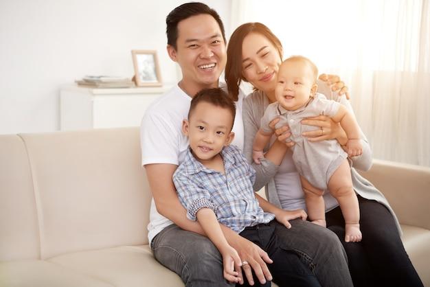 Liebevolle asiatische paare, die zu hause auf couch mit jungem sohn und baby aufwerfen Kostenlose Fotos