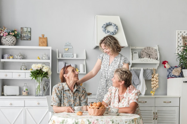 Liebevolle frauen aus drei generationen, die zu hause frühstücken Kostenlose Fotos