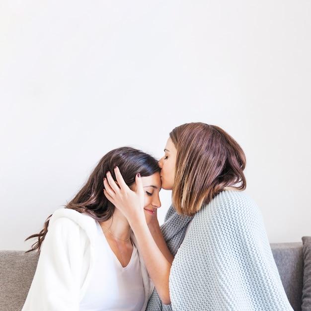 Liebevolle frauen kuscheln zu hause küssen Kostenlose Fotos