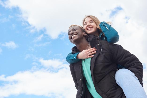 Liebevolle junge internationale paare auf himmel-hintergrund. afrikanischer kerl und kaukasische frau Premium Fotos