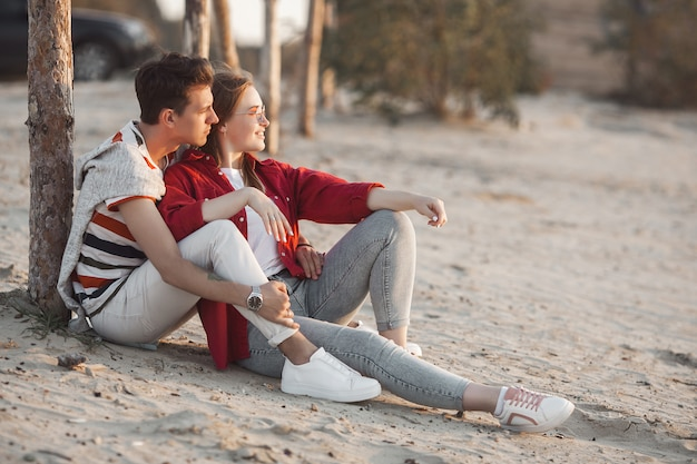 Liebevolle junge paare auf sonnenuntergang auf dem strand. liebe. mann und frau umarmen im sommer. Premium Fotos