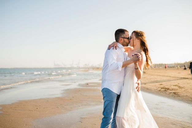 Liebevolle junge paare, die die hand des anderen sich küssen am sommerstrand halten Kostenlose Fotos