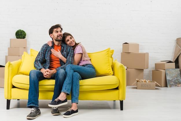 Liebevolle lächelnde junge paare, die auf dem gelben sofa in ihrem neuen haus sitzen Kostenlose Fotos
