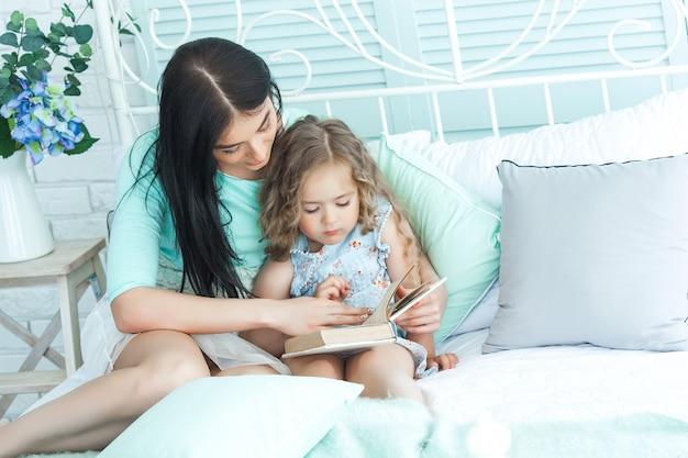 Liebevolle mutter, die ihrem kind eine gute-nacht-geschichte vorliest Premium Fotos