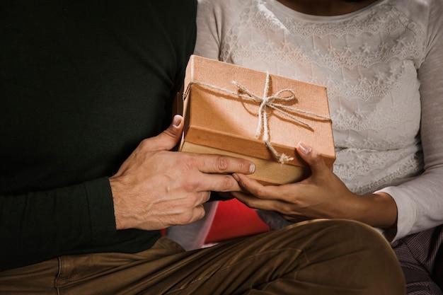 Liebevolle paare, die ein geschenk halten Kostenlose Fotos