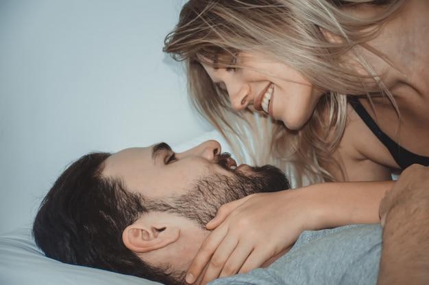 Liebevolle paare, die im bett küssen glückliche paare, die zusammen im bett liegen. Premium Fotos