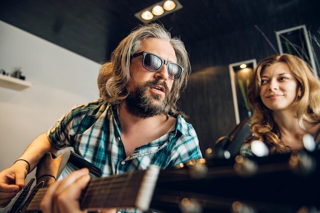 Liebevoller mann, der gitarre für seine frau spielt Premium Fotos