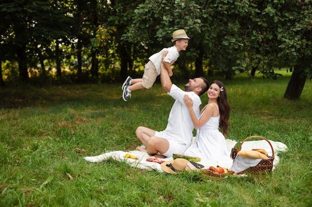 Liebevoller vater, der mit sohn spielt, während schöne mutter ihren ehemann von hinten umarmt. glückliche kaukasische familie, die sommertag im park oder im wald beim picknick auf dem gras genießt. Premium Fotos