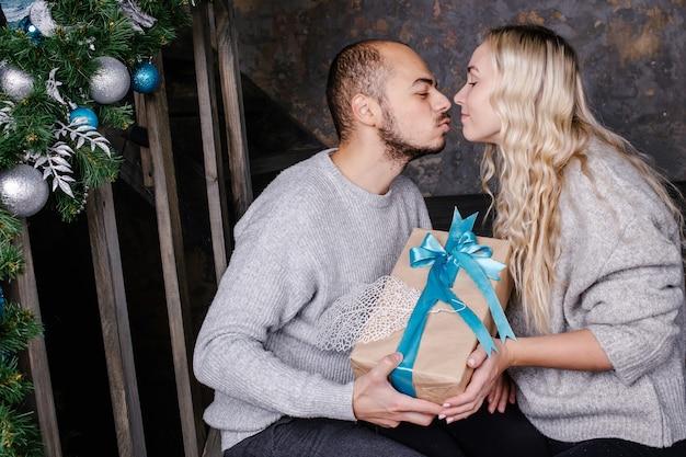 Liebevolles junges paar tauscht geschenke für das neue jahr aus. ehemann küsst seine frau und gibt ein geschenk für das neue jahr. weihnachts- und neujahrsgeschenk zu hause. Premium Fotos
