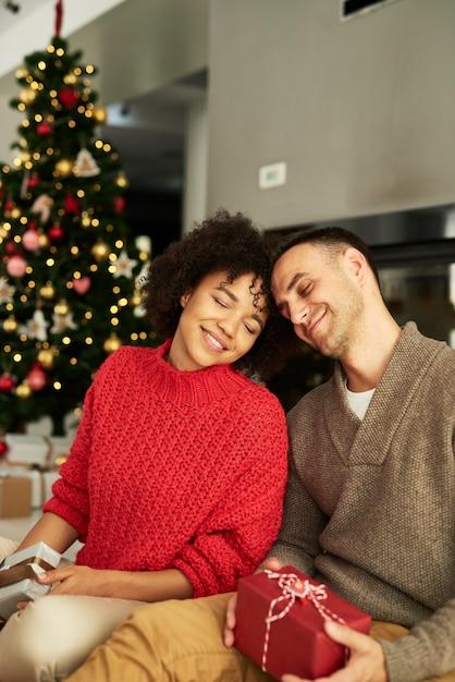 Liebevolles paar, das weihnachtsgeschenke austauscht Kostenlose Fotos