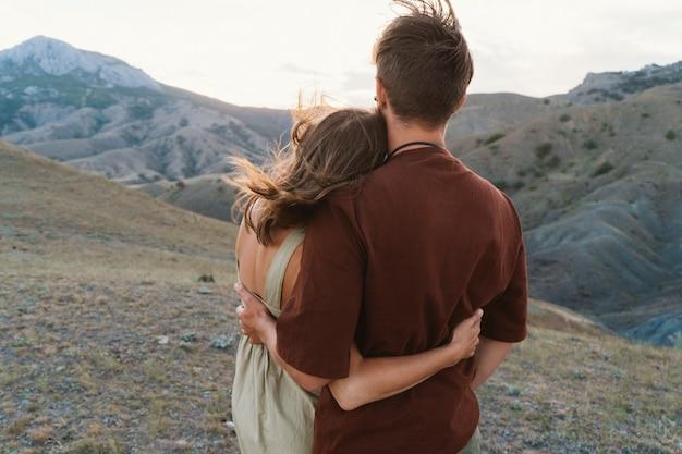 Liebhaber genießen den sonnenuntergang. der mann und das mädchen stehen und umarmen sich. romantisches date auf dem gipfel des berges. valentinstag wird von liebenden gefeiert. Premium Fotos