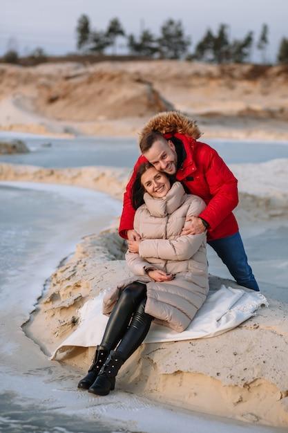 Liebhaber in daunenjacken auf den dünen von sandgruben, um die sich das eis dreht Premium Fotos