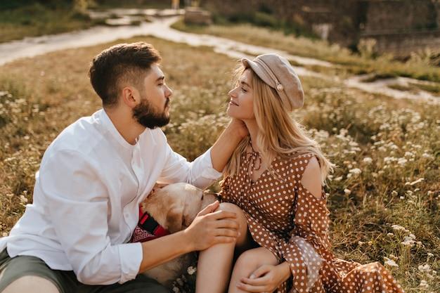 Liebhaber schauen sich sanft in die augen und sitzen im park auf gras neben dem hund. mann streichelt sanft seine freundin. Kostenlose Fotos