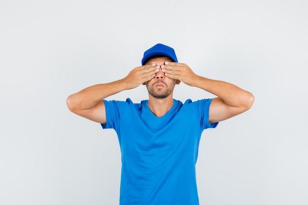 Lieferbote, der augen mit händen im blauen t-shirt bedeckt Kostenlose Fotos