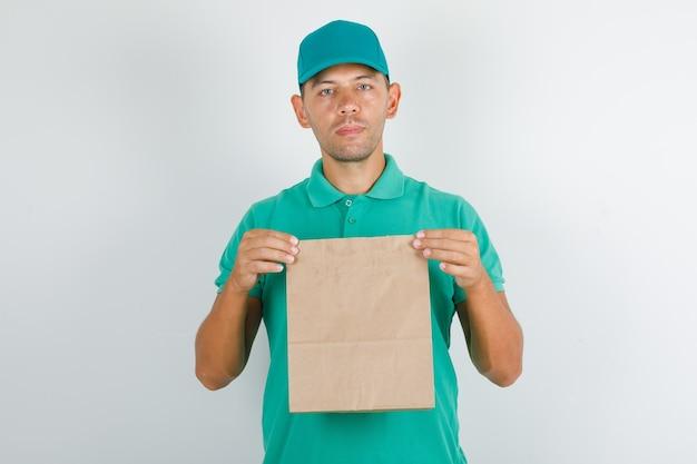 Lieferbote, der braune papiertüte im grünen t-shirt mit kappe hält Kostenlose Fotos