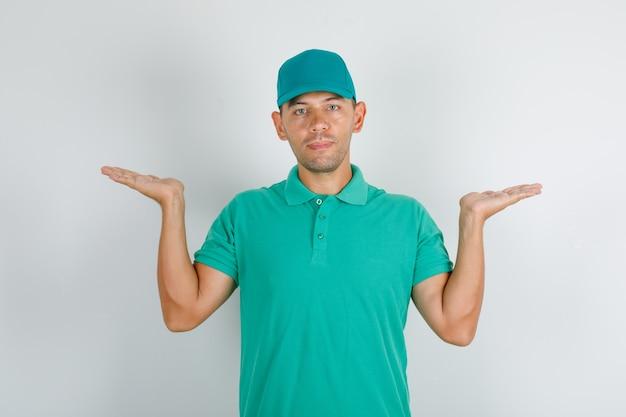 Lieferbote, der leere hände im grünen t-shirt mit kappe hält Kostenlose Fotos