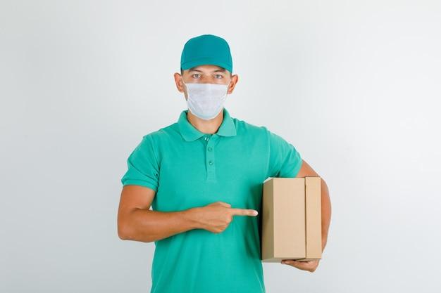 Lieferbote, der pappkarton im grünen t-shirt mit kappe und maske hält Kostenlose Fotos