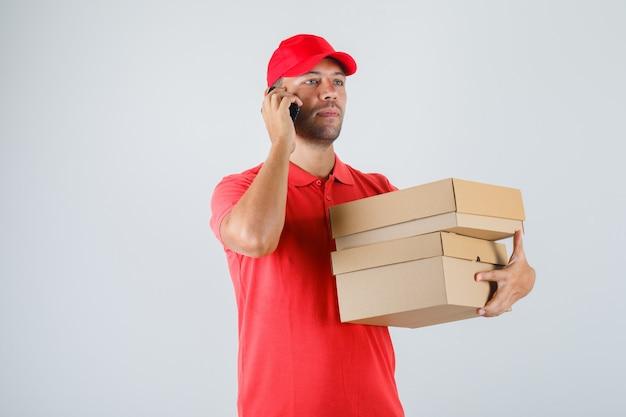 Lieferbote, der pappkartons hält, während auf handy in roter uniform sprechen Kostenlose Fotos