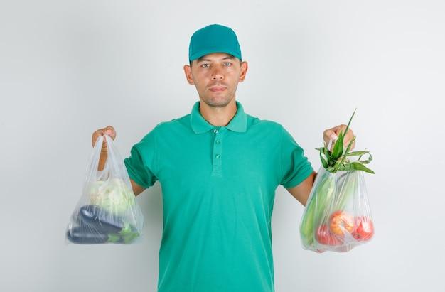 Lieferbote, der plastiktüten mit gemüse im grünen t-shirt mit kappe hält Kostenlose Fotos