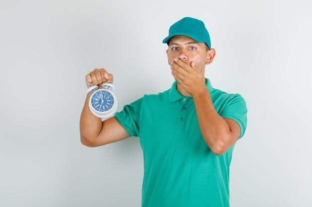 Lieferbote, der wecker im grünen t-shirt und in der kappe hält und besorgt schaut Kostenlose Fotos