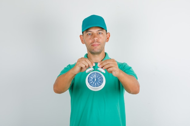Lieferbote, der wecker im grünen t-shirt und in der kappe hält und positiv schaut Kostenlose Fotos