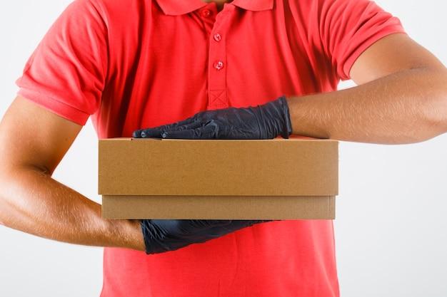 Lieferbote hält pappkarton in roter uniform, medizinische handschuhe, vorderansicht. Kostenlose Fotos