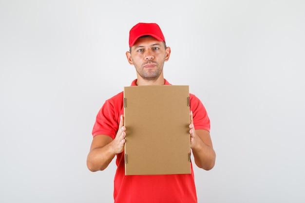 Lieferbote hält pappkarton in roter uniform. vorderansicht. Kostenlose Fotos
