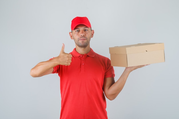 Lieferbote hält pappkarton und zeigt daumen hoch in roter uniform und sieht positiv aus. Kostenlose Fotos