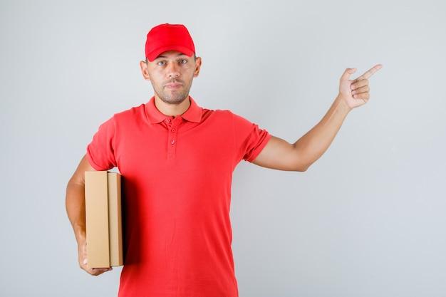Lieferbote hält pappkarton und zeigt in roter uniform weg Kostenlose Fotos