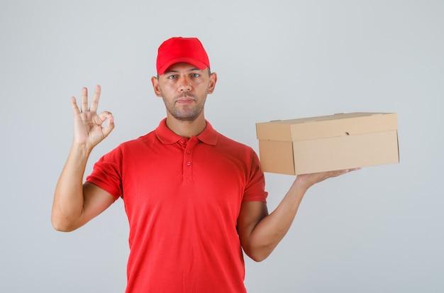 Lieferbote hält pappkarton und zeigt ok-zeichen in roter uniform Kostenlose Fotos