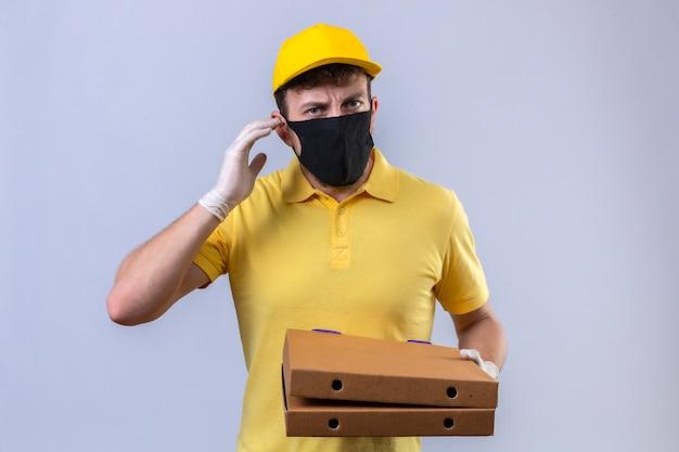 Lieferbote im gelben poloshirt und in der kappe tragen schwarze schutzmaske, die schwerhörige pizzaschachteln hält, die mit finger nahe ohr auf lokalisiertem weiß stehen Kostenlose Fotos