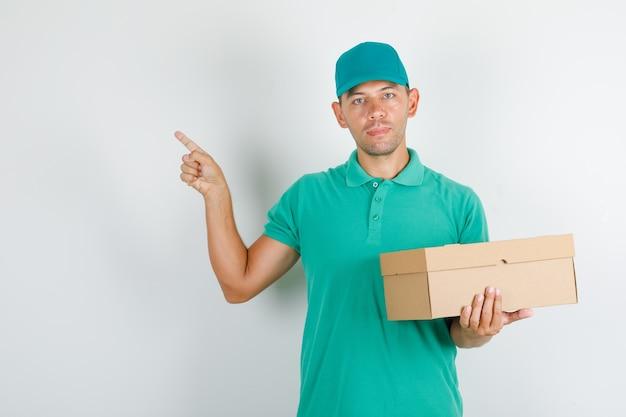 Lieferbote im grünen t-shirt und in der kappe, die etwas mit pappkarton zeigen Kostenlose Fotos
