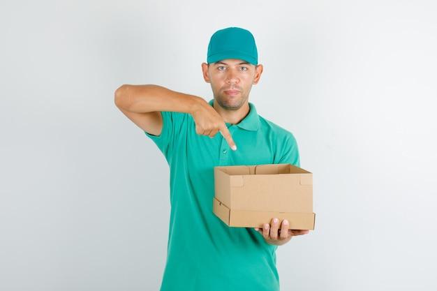 Lieferbote im grünen t-shirt und in der kappe, die pappkarton zeigt Kostenlose Fotos