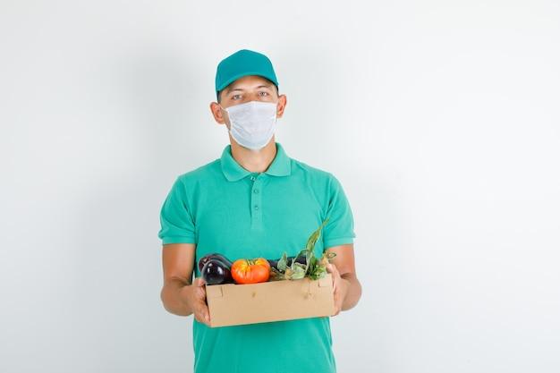 Lieferbote im grünen t-shirt und in der kappe, maske, die gemüsebox hält Kostenlose Fotos