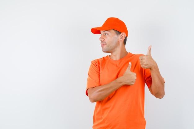 Lieferbote im orangefarbenen t-shirt und in der kappe, die daumen hoch zeigen, während sie beiseite schauen und fröhlich schauen Kostenlose Fotos