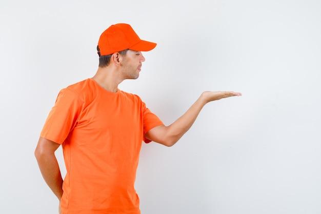 Lieferbote im orangefarbenen t-shirt und in der kappe, die erhabene handfläche ausbreiten, andere hand verstecken und joker schauen, vorderansicht. Kostenlose Fotos