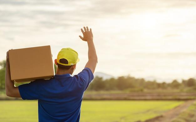Lieferer, der braune paket- oder pappschachtellieferung zum kunden an der landschaft hält Premium Fotos