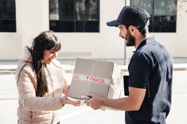 Lieferer, der paket an weiblichen kunden liefert Kostenlose Fotos