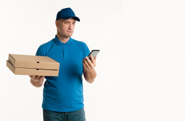 Lieferer, der pizzakästen beim betrachten des telefons hält Kostenlose Fotos