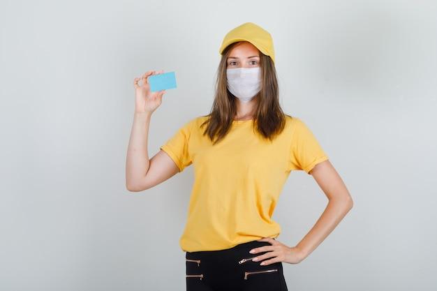 Lieferfrau, die blaue karte im t-shirt, in der hose und in der mütze, in der maske hält und froh schaut Kostenlose Fotos