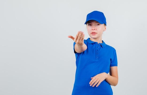 Lieferfrau, die einlädt, im blauen t-shirt und in der mütze zu kommen Kostenlose Fotos