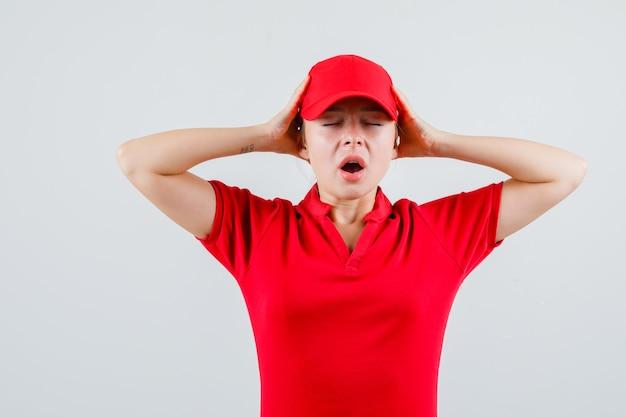 Lieferfrau, die hände zum kopf im roten t-shirt und in der mütze hält und genervt aussieht Kostenlose Fotos