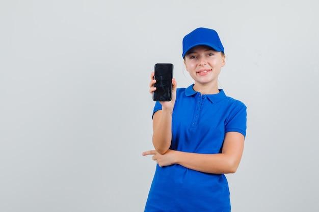 Lieferfrau, die handy im blauen t-shirt und in der kappe hält und fröhlich schaut Kostenlose Fotos