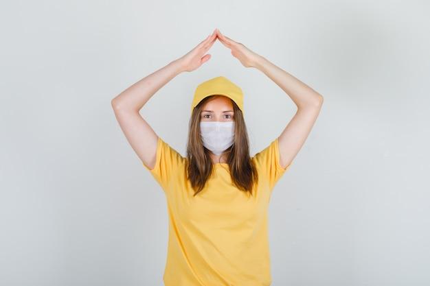 Lieferfrau, die hausdachzeichen über kopf in t-shirt, kappe, maske tut und froh schaut Kostenlose Fotos